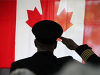 Police officer salutes the Canadian Flag in Windsor