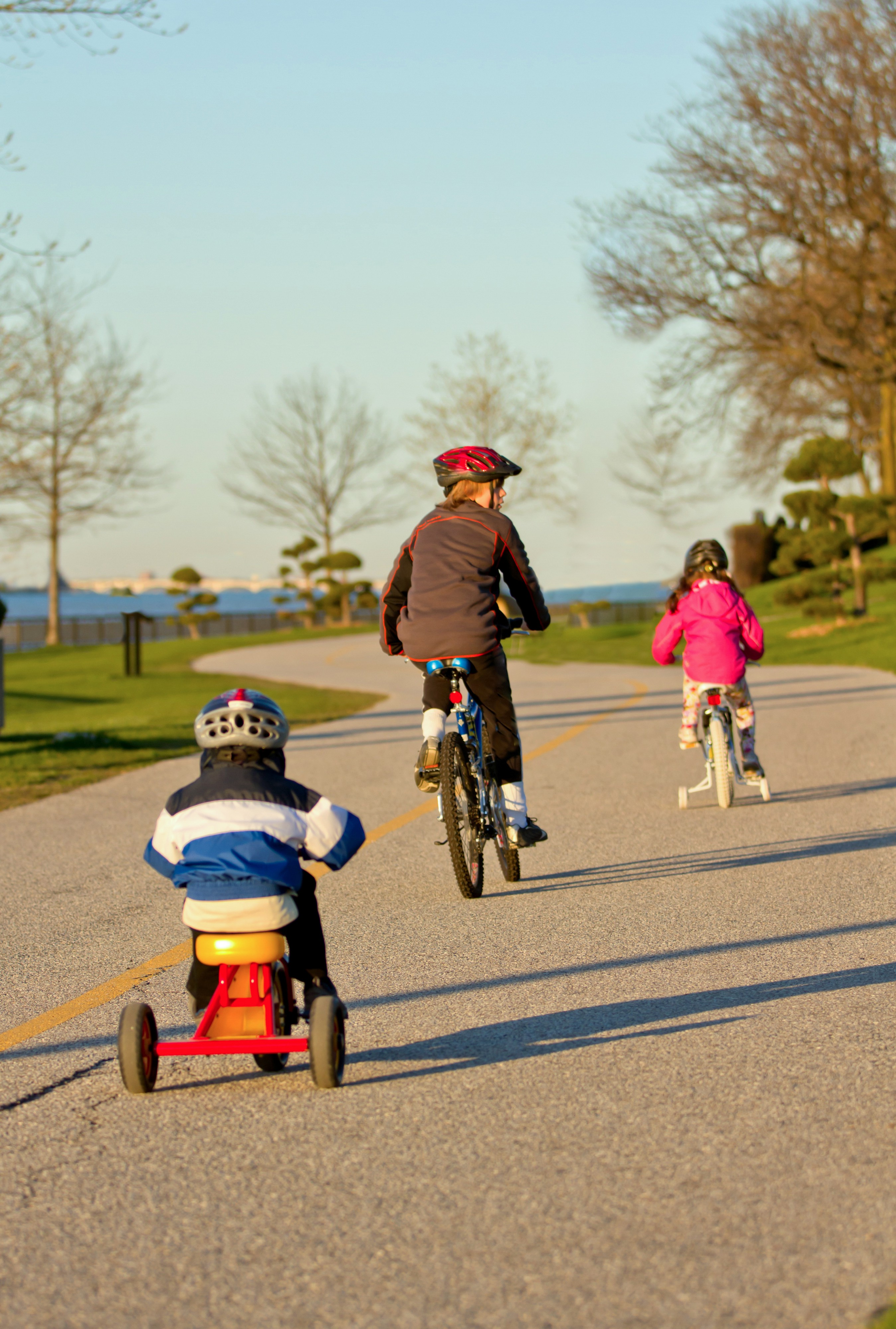 Adults and children biking along the riverfront