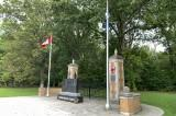 Granite monument with plaques and flags at park gates.