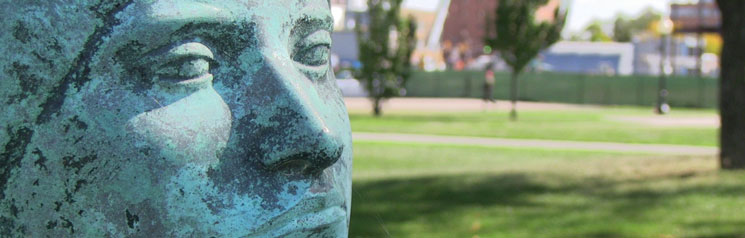 Sculpted bronze face with park background