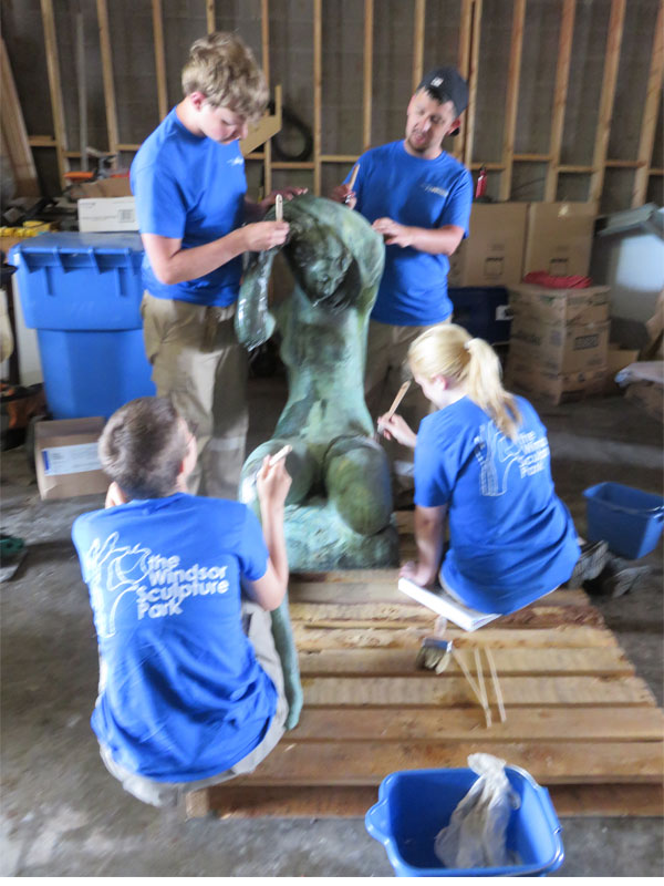 Summer students clean sculptures