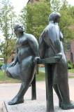 Bronze sculpture of two ladies leaning against a horizontal bar.