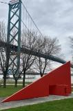 Painted steel sculpture on a riverfront.
