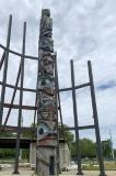 Large painted totem pole overlooking the water.