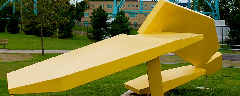 Large, painted yellow, steel sculpture in a park.