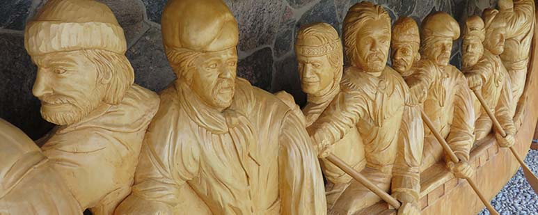 Detail of a lifesize carved wood sculpture of nine men in a long canoe.