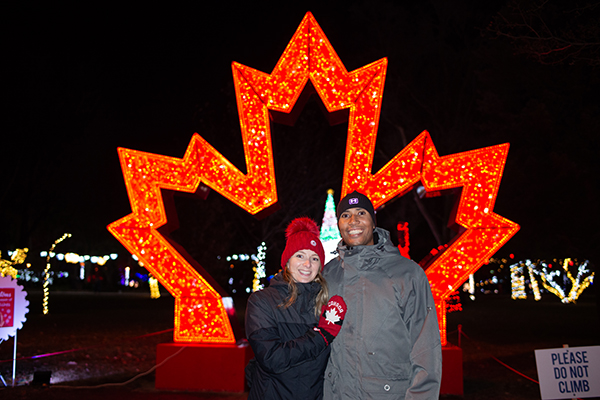 Couple posing in front of illuminated maple leaf
