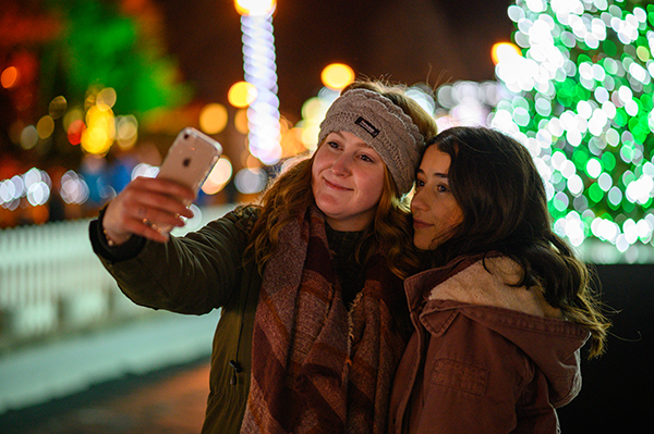 Girls snap a selfie in front of the tree
