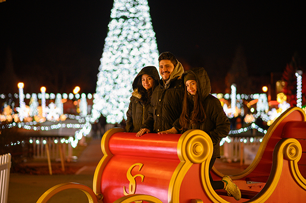 Family poses in the Santa Clause sleigh