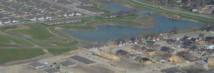 Overhead view of a subdivision and small lake