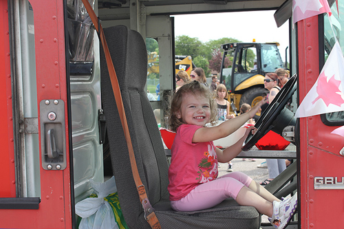 Little girl at the wheel of a big truck