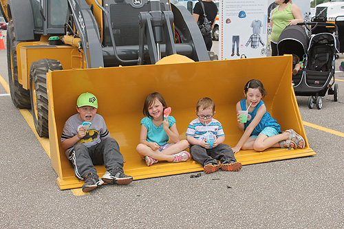 Boys and girls in a bulldozer scoop
