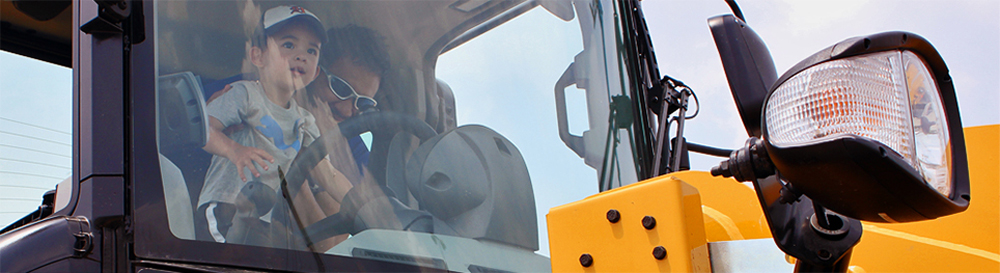 A father and son sit in the cab of a construction vehicle
