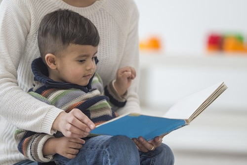 Young boy being read to in caregiver's lap