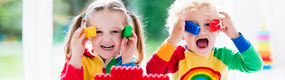 Boy and girl playing with multicoloured blocks