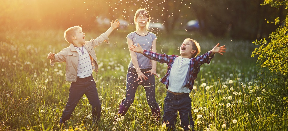 Three children playing among dandelion tufts