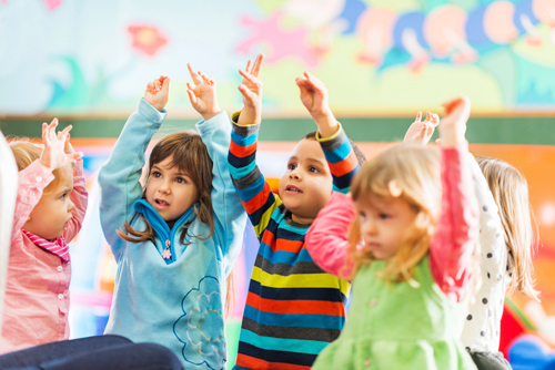 Children raising their hands in class