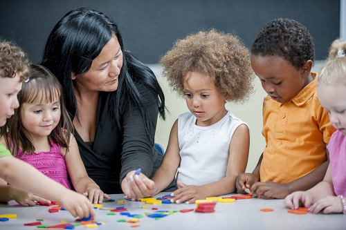 Early learning professional playing with a puzzle with children