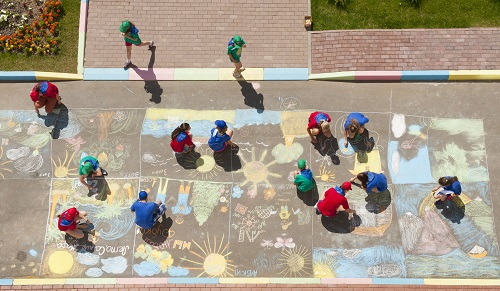 Overhead view of kids and adults making sidewalk chalk art