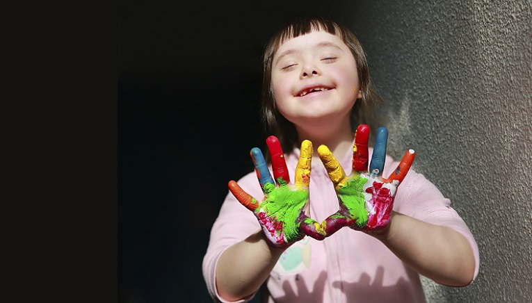 Smiling child with colourfully painted hands