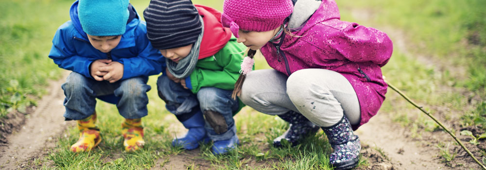Three children look at the ground outdoors
