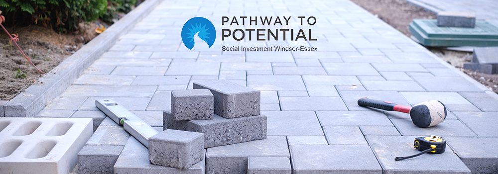 A stone path under construction with the Pathway to Potential logo on it.